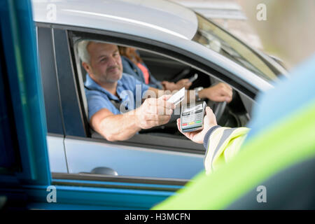 Driver in car paying toll booth at bridge using contactless card payment technology - Stock Photo