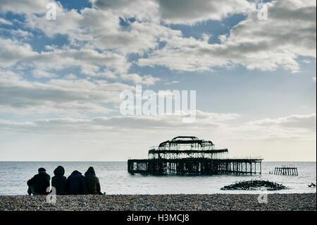 Tourists relaxing on Brighton beach, England - Stock Photo