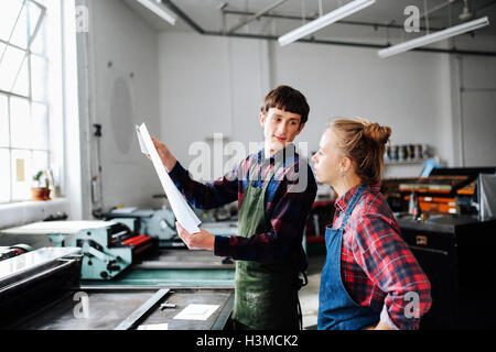Young male and female craftsperson looking at print in book arts workshop - Stock Photo