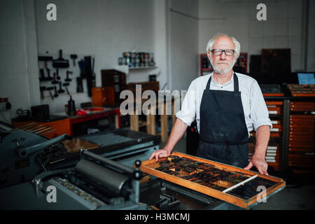 Portrait of senior craftsman next to tray of letterpress letters in print workshop - Stock Photo