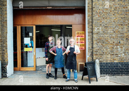 Family portrait of senior craftsman with daughter and son outside print workshop - Stock Photo