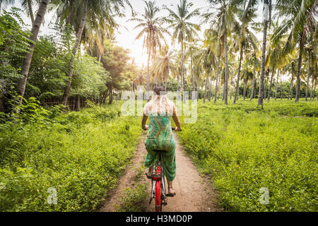 Rear view of young woman cycling in palm tree forest, Gili Meno, Lombok, Indonesia - Stock Photo