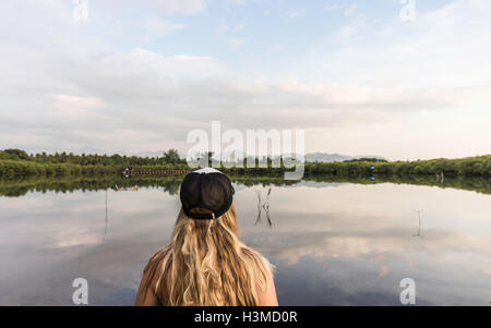 Rear view of young woman looking out over lake, Gili Meno, Lombok, Indonesia - Stock Photo