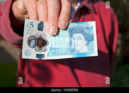 Man holding new polymer five pound note England UK United Kingdom GB Great Britain - Stock Photo