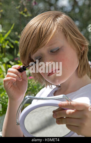 young boy putting makeup on pretending to be a girl - Stock Photo