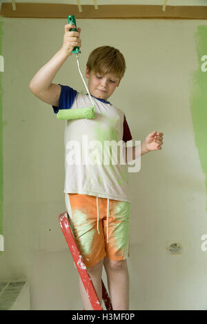 young boy painting his T-shirt - Stock Photo