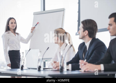 Business woman speaking at presentation and pointing to white board - Stock Photo
