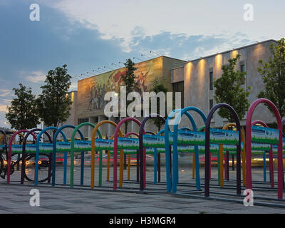 Multi coloured bicycle rack in front of the Natural History Museum at dusk. - Stock Photo
