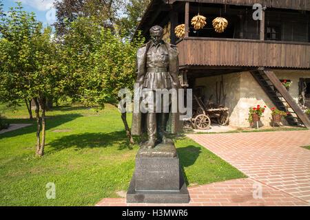 House and bronze statue of Marshal Tito in Kumrovec, Croatia - Stock Photo