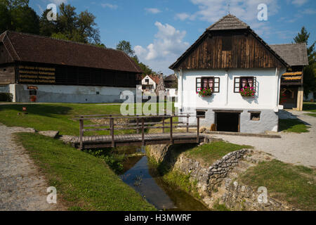 Traditional house  and buildings  by a stream  in Kumrovec, Croatia - Stock Photo