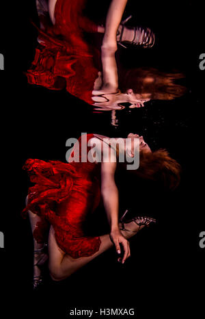 Underwater view of girl wearing red dress and high heeled shoes, reflected in water surface