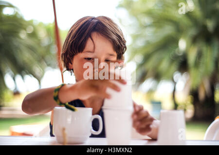 Boy balancing plastic cups - Stock Photo
