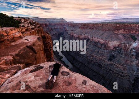 Man lying on rock, looking at view, Torroweap Overlook, Grand Canyon, Torroweap, Arizona, USA - Stock Photo