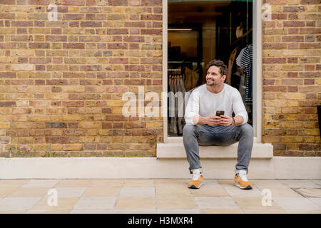 Young man with smartphone sitting on doorstep, Kings Road, London, UK - Stock Photo