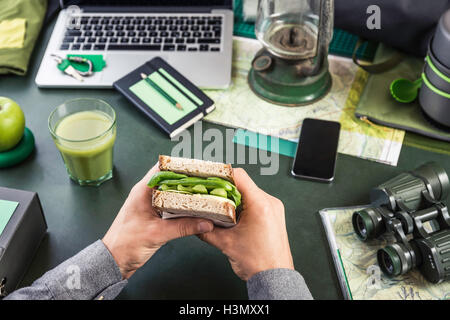 Mans hand's holding sandwich at table with hiking equipment and laptop Stock Photo