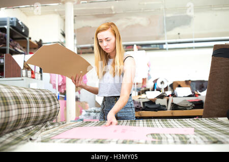 Young woman working in leather jacket manufacturers - Stock Photo