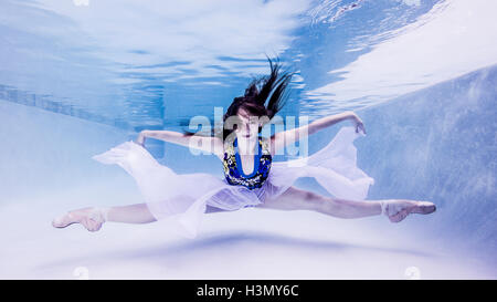 Underwater view of teenage girl, wearing ballet shoes, in dance position - Stock Photo