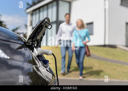 Man and woman walking towards electric car being charged - Stock Photo