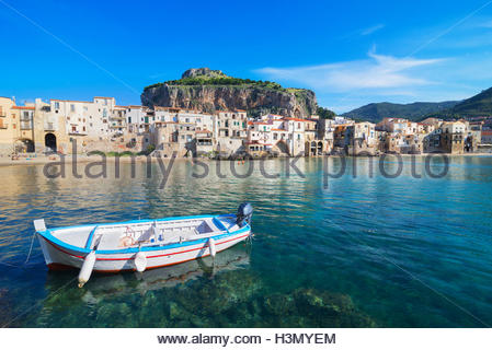 Fisherman's boat near old town waterfront and La Rocca, Cefalu, Sicily, Italy - Stock Photo