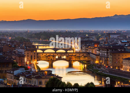 View of Florence at sunset with the Ponte Vecchio bridge over the Arno River - Stock Photo