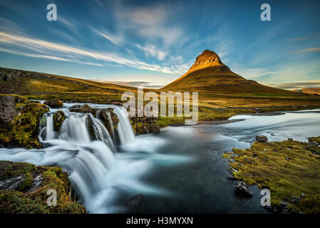 Summer sunset over the famous Kirkjufellsfoss Waterfall with Kirkjufell mountain in the background in Iceland. Long - Stock Photo