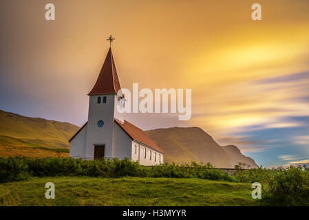 Sunrise over the lutheran church  on a mountain top in the town of Vik in Iceland. Long exposure. - Stock Photo