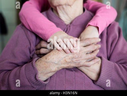 Unrecognizable granddaughter holding hands of her grandmother - Stock Photo