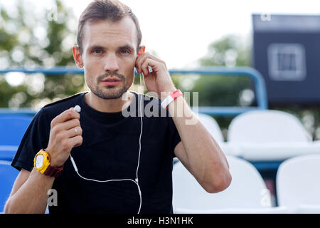 Sporty young male listening to music on headphones in stadium - Stock Photo