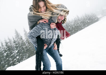 Couple in love, man giving woman piggyback. Winter nature. - Stock Photo