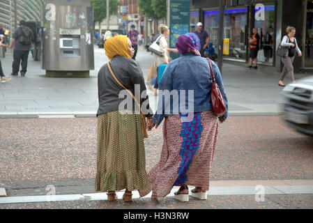 Asian refugee dressed Hijab scarf on street in the UK everyday scene - Stock Photo