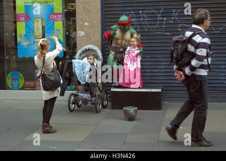 Glasgow street scenes family self portrait using fancy dress  street busker ninja turtle child as princess - Stock Photo