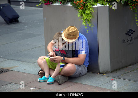 Glasgow street scenes father and son use mobile phone together while sitting on ground - Stock Photo