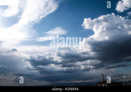 Stormy clouds in a middle of a spring sunny day over the city - Stock Photo