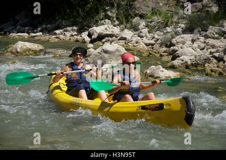 Tourism, water-sports, tourists. Two young women canoeing down the fast flowing turbulent waters of the Drôme River. - Stock Photo