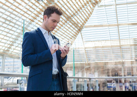 Businessman writing a message on smartphone, train station waiting lounge in background - Stock Photo
