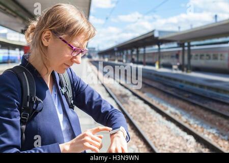 Business woman using smart watch at train station - Stock Photo