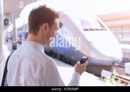 Young adult male using app on smartphone during business travel with train in background - Stock Photo
