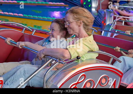 mother and son on the ride ´action´, Dom, Hamburg, Germany - Stock Photo