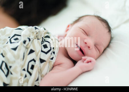 Sleeping baby boy smiling - Stock Photo