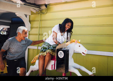 Senior woman on horse funfair ride, senior man standing beside her, laughing, Long Beach, California, USA - Stock Photo