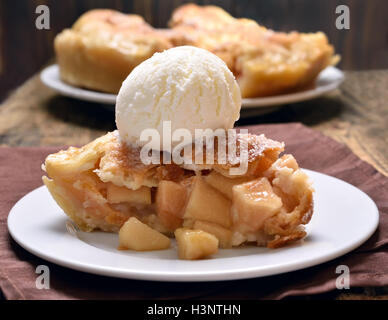 Piece of apple pie served with ice cream, close up view - Stock Photo