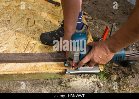 Men using an electric saw to cut a plank - Stock Photo