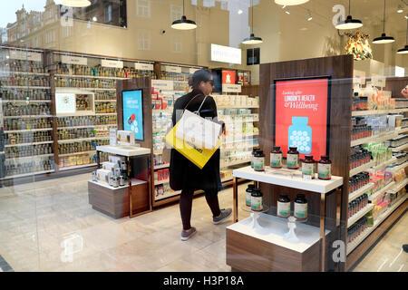 A woman shopping in a drugstore chemist shop in Marylebone, West London UK  KATHY DEWITT - Stock Photo