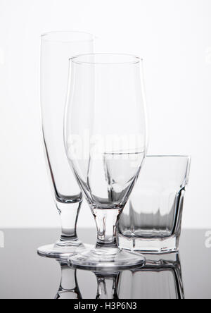 Beer and whiskey glasses on black reflecting board on white background - Stock Photo
