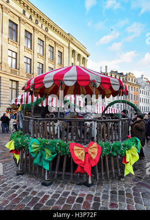Riga, Latvia - December 25, 2015: People at carousel at Christmas market on Dome square in old Riga. - Stock Photo