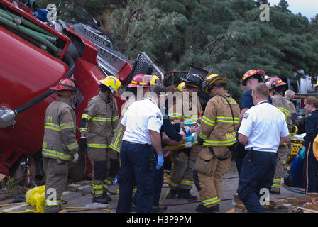 Rescue workers remove drivers from overturned tank truck - Stock Photo