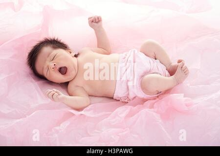 MODEL RELEASED. Newborn baby girl in pink nappy, yawning. - Stock Photo