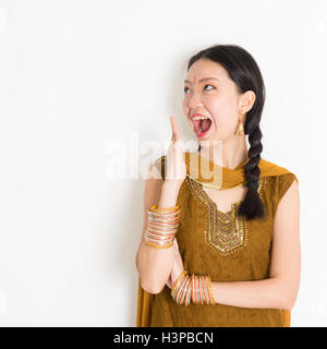 Portrait of shocked mixed race Indian Chinese woman in traditional punjabi dress opened mouth wide, surprised emotion, - Stock Photo