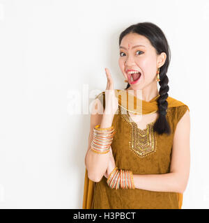 Portrait of shocked mixed race Indian Chinese girl in traditional punjabi dress opened mouth wide, surprised emotion, - Stock Photo