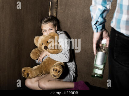 Sad little girl sitting against the wall in despair. In his hands he holds an teddy bear. drunken man threatens. - Stock Photo